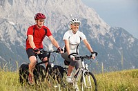 Couple cycling across a meadow