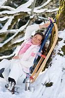 Woman with sledge leaning on tree