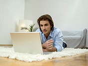 Man lying on floor, using laptop