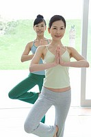 Two Young Women Practicing Yoga, Standing on One Foot, Putting Palm Together, Front View