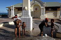 Mid adult woman and a young woman bathing with their children, Muizenberg, False Bay, Cape Town, Western Cape Province, South Africa