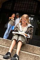 A young teenage student studying on the steps