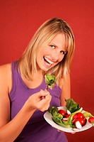 A young woman eating fresh vegetables