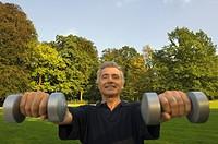 A mature man lifting dumbbells