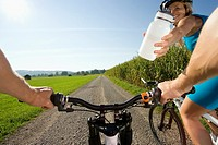 A woman giving her friend a bottle of water while cycling