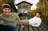 Friends relaxing outside a cottage near the lake