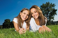 Two teenage friends lying on the grass