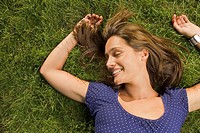 A teenage girl lying down on the grass