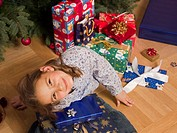 A girl sitting with Christmas presents