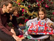 Girl opening her Christmas present, her father and brother look on
