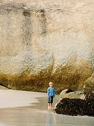 Boy standing near the rocks on the beach
