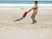 A father playing with his daughter on the beach