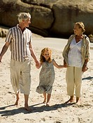 A girl walking on the beach with her grandparents
