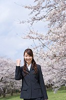 Portrait of a woman standing at the field of cherry blossoms, smiling and looking at camera, front view, Japan