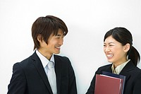 Young businesswoman and businessman smiling and talking, woman holding files, front view, white background, Japan
