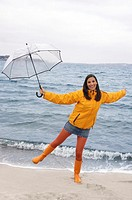 Portrait of a young woman holding an umbrella on the beach