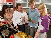 Male chef teaching three students in the kitchen
