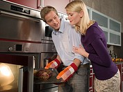 Side profile of a young couple putting a dish into a microwave