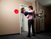 Man carrying his girlfriend into a hotel room