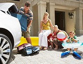 Family Waiting While Dad Packs Car for Vacation