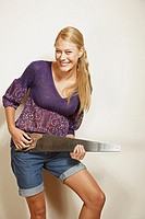 Portrait of a young woman pretending to play a guitar with a saw