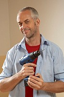 Portrait of a mid adult man holding a drill