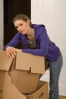 A young woman bending over cardboard boxes