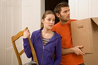Young woman holding a chair with a young man carrying a cardboard box