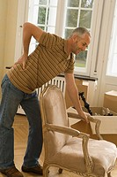 Mid adult man bending over an armchair