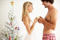 Affectionate Young Couple Giving Present at Christmas