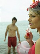 Close-up of a young woman holding a snorkel with a young man standing on the beach