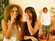 Close-up of two young women covering their mouths with their hands