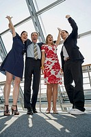 Two businessmen and two businesswomen cheering with their hands raised