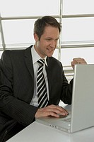 Businessman using a laptop and smiling