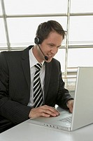 Businessman using a laptop and wearing a headset