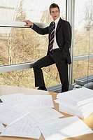 Businessman standing against a glass wall