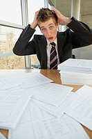 Businessman sitting with documents and looking worried