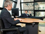 Two businessmen walking in their office