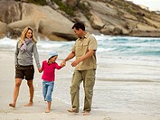 Parents walking on the beach with their daughter