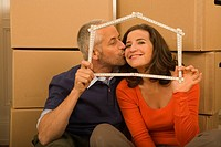 Mid adult man kissing a young woman and holding a scale in the shape of a house