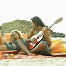 Young man playing the guitar with a young woman lying beside him