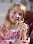 Close-up of a girl holding a horse shoe locket and smiling