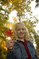 Young girl holding autumn leaf
