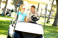 Couple driving golf cart