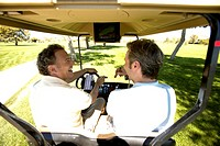 Men driving golf cart