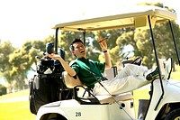 Asian man relaxing with cigar in golf cart