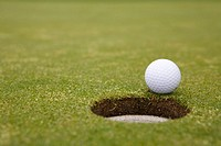Golf ball rolling towards hole