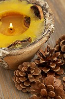 Perfumed candle and pine cones