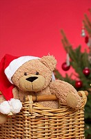 Teddy bear wearing Santa Claus hat in a basket