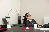 Businessman wearing sleeping mask sitting at desk